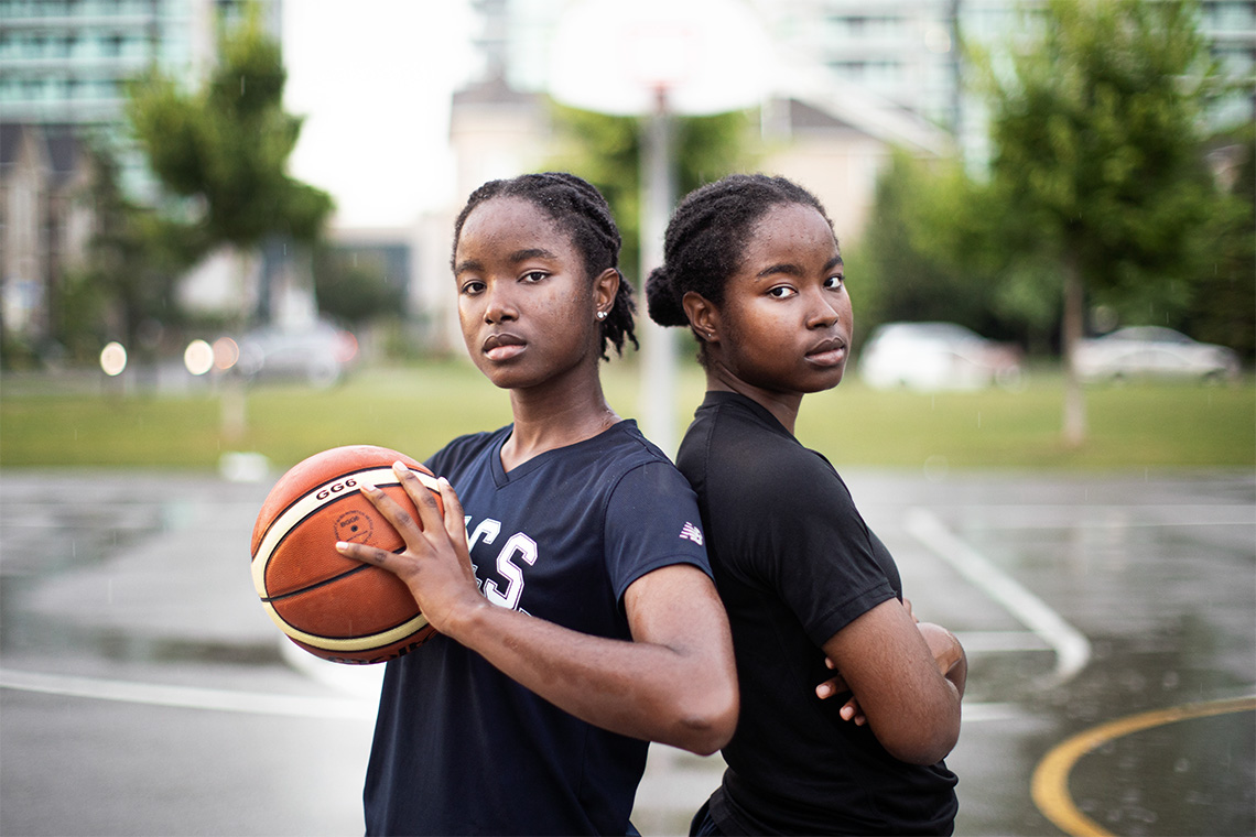 Mikhaela and Nakeisha Ekwandja pose on a rainy downtown basketball court