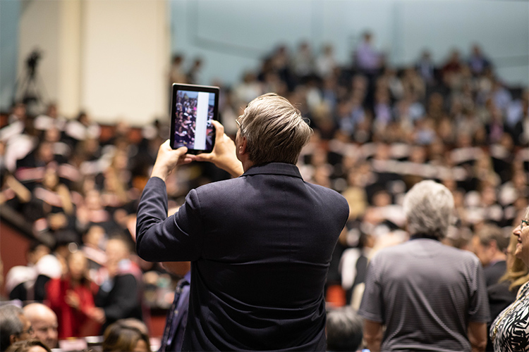An older man takes a photo with his ipad inside convocation hall