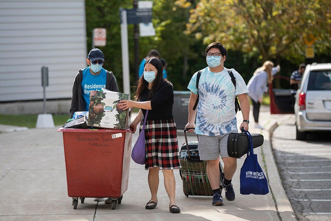 a pair of students, helped by a volunteer, bring their belongings to residence at UTM