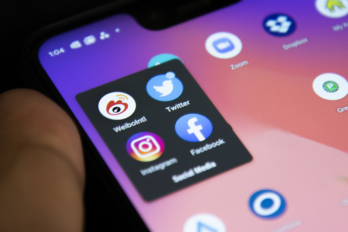 close up of cell phone screen with weibo, twitter, instragram and facebook icons