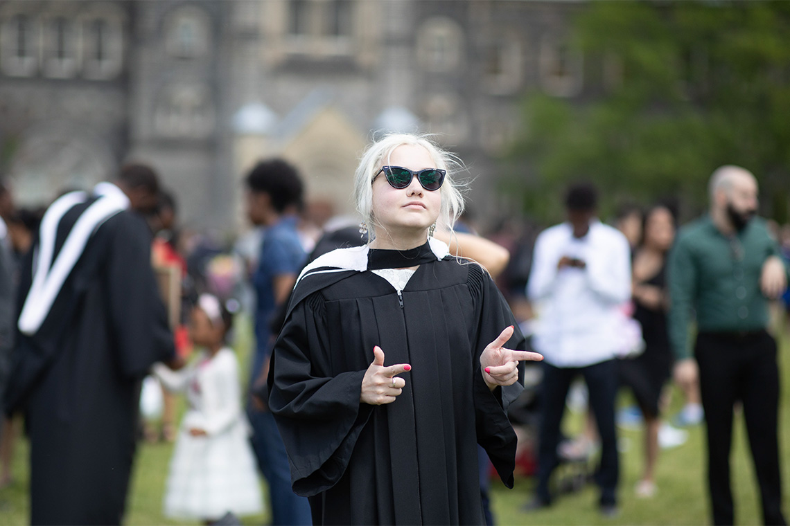 Elspeth Arbow in her graduation robe with sunglasses on and finger pointing in front of University College