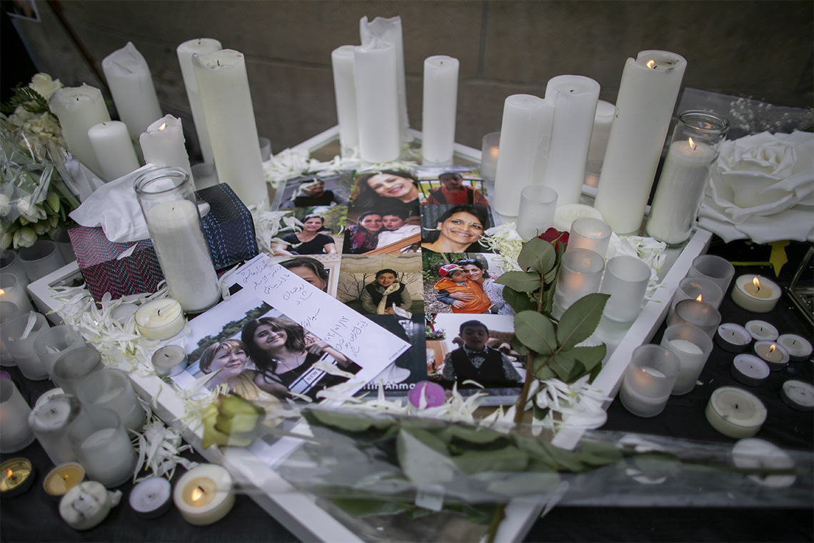 a table with lit candles, flowers and photos of the victims of the PS752 plane crash