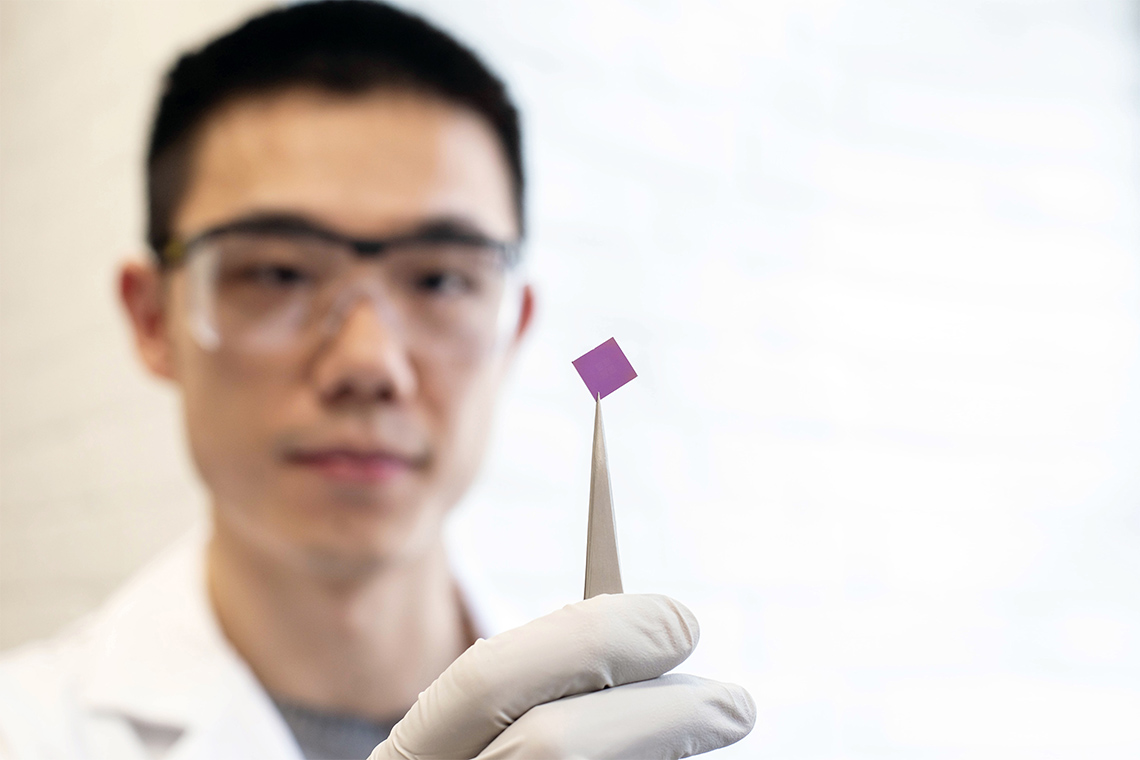 Researcher Teng Cui holds up a small pink square silicon chip that was used to stretch the graphene over