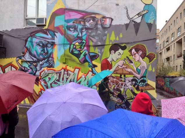 photo of students under umbrellas surveying graffiti