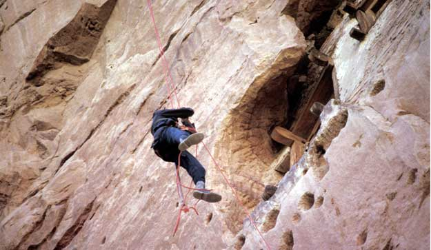 photo of Gevers dangling from rope and examining cliff face