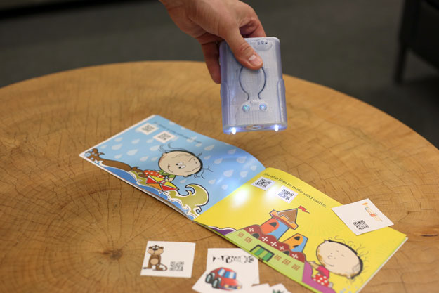 photo of hand holding Attollo device as it reads a children's book