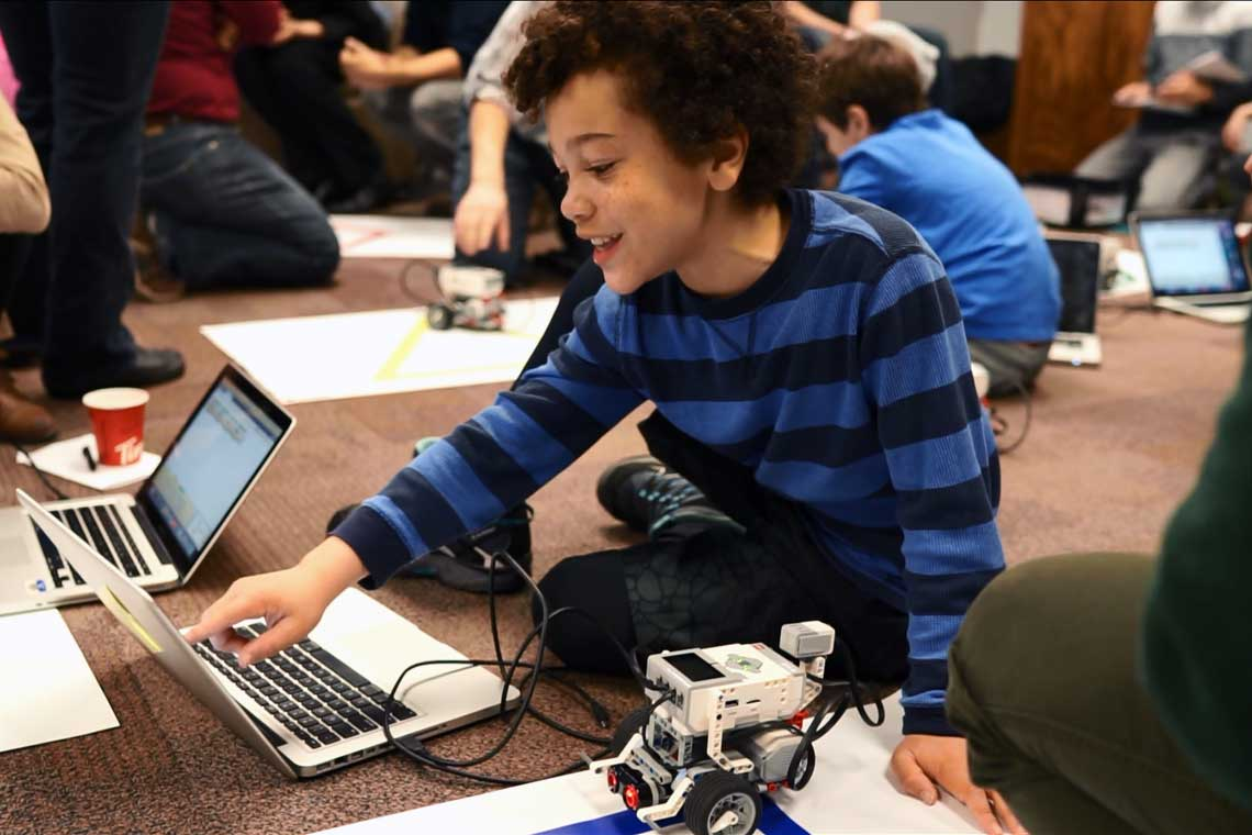 photo of kids playing and learning with laptops and robots