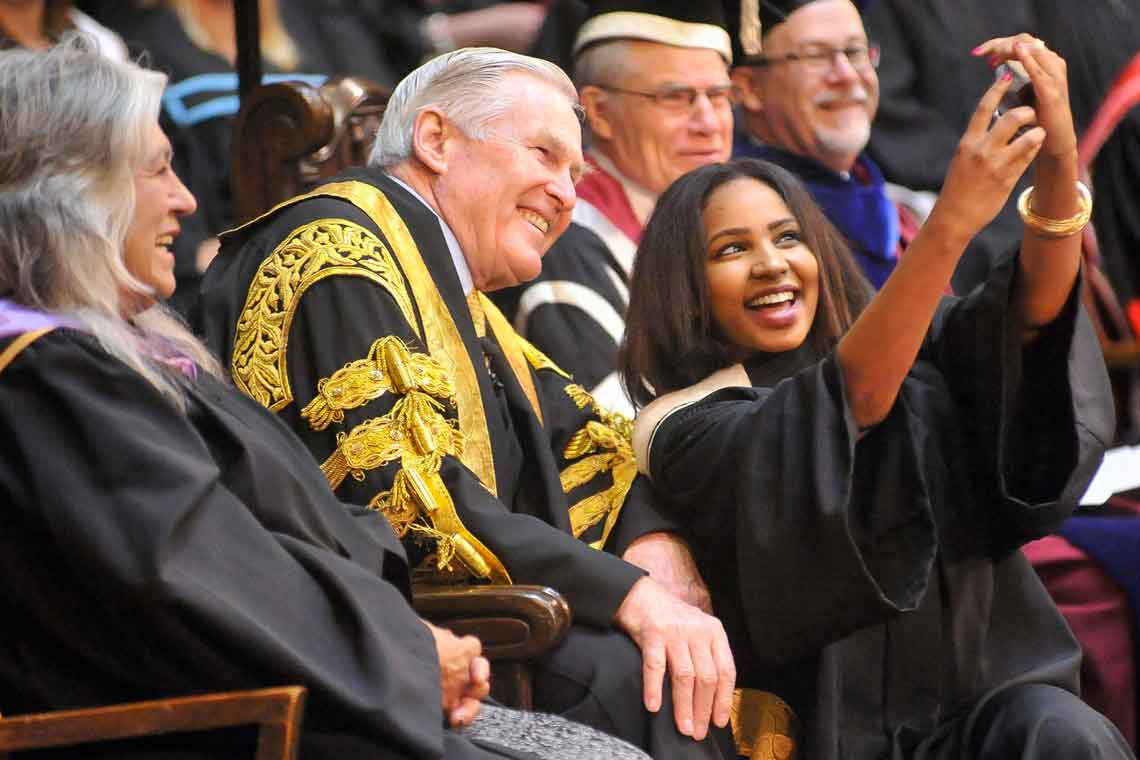 photo of graduating student taking selfie with chancellor