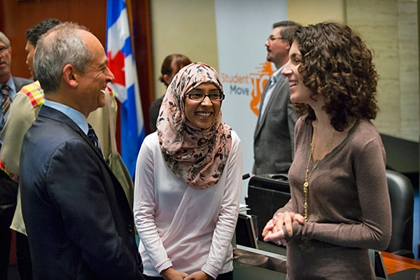 A photo of two students talking to President Gertler