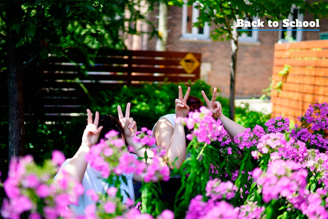 Two students hiding in the flowers, making peace signs