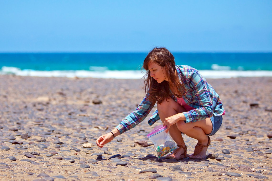 photo of Rochman on beach collecting debris