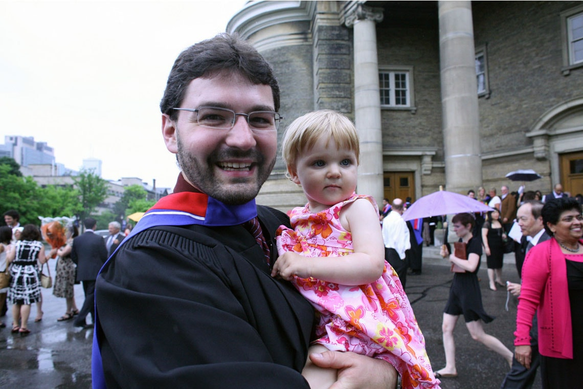 photo of grad with child in his arms