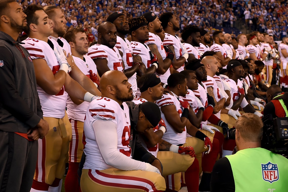photo of football players taking a knee