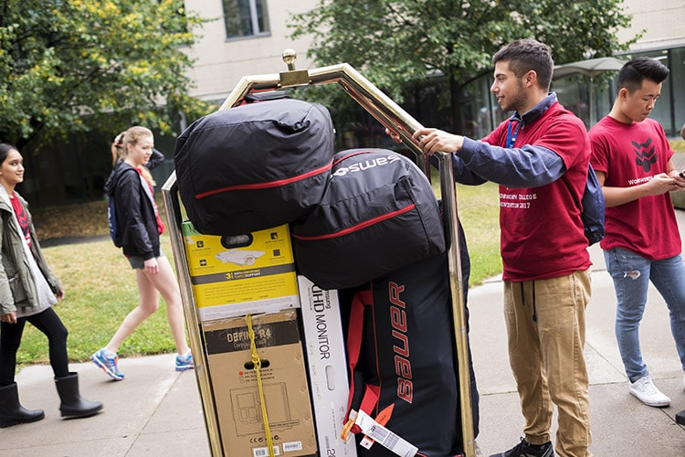 Justin Zelnicker pushing hotel cart outside Woodsworth College