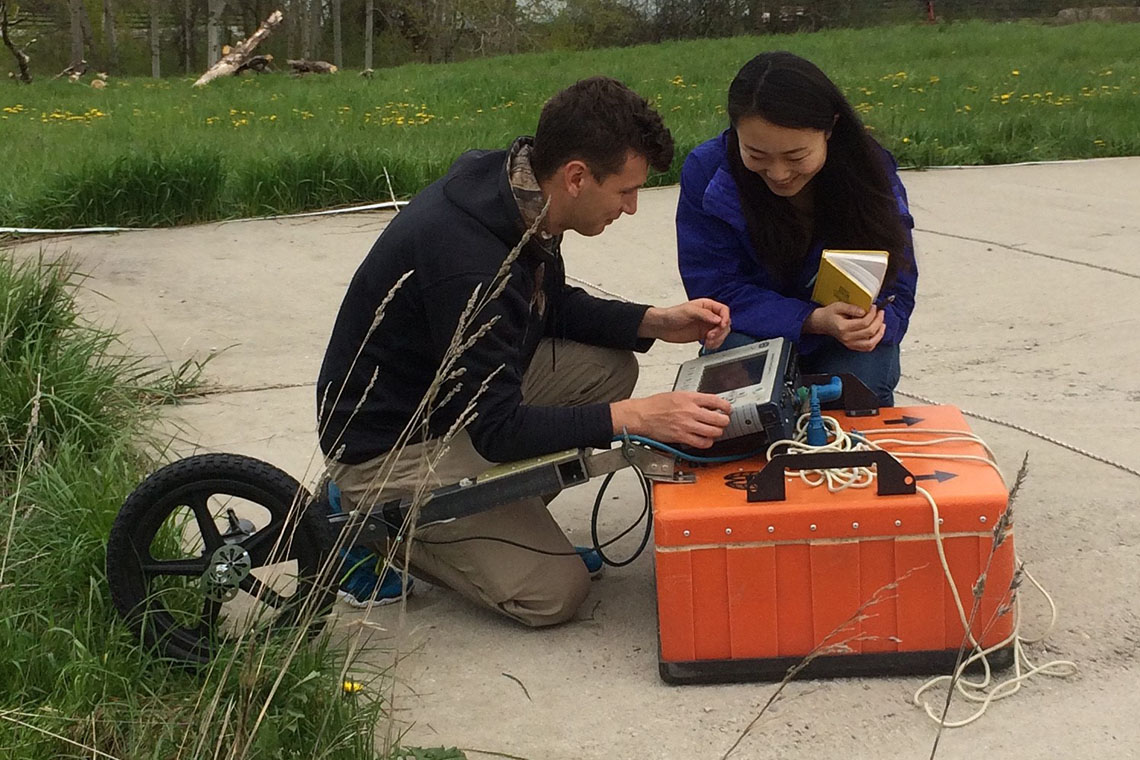 Photo of students taking measurements with ground-penetrating radar