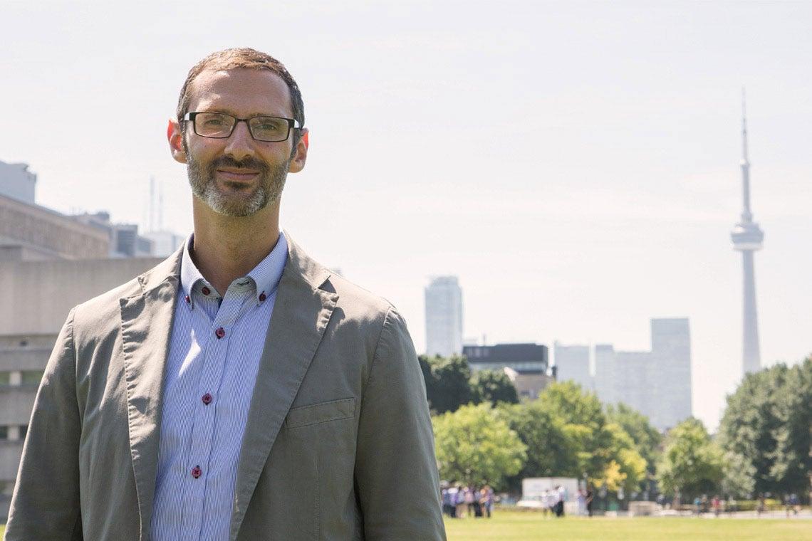 photo of Matti Siemiatycki with Toronto skyline in background