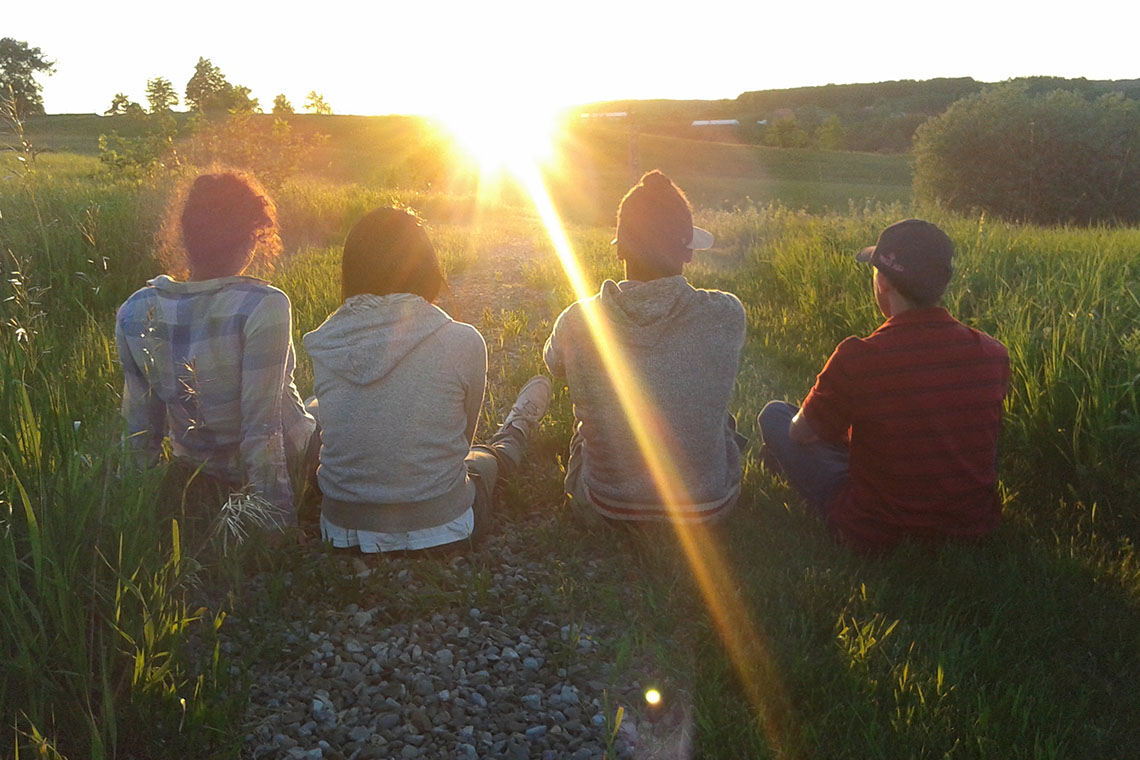 Photo of students on farm during sunset