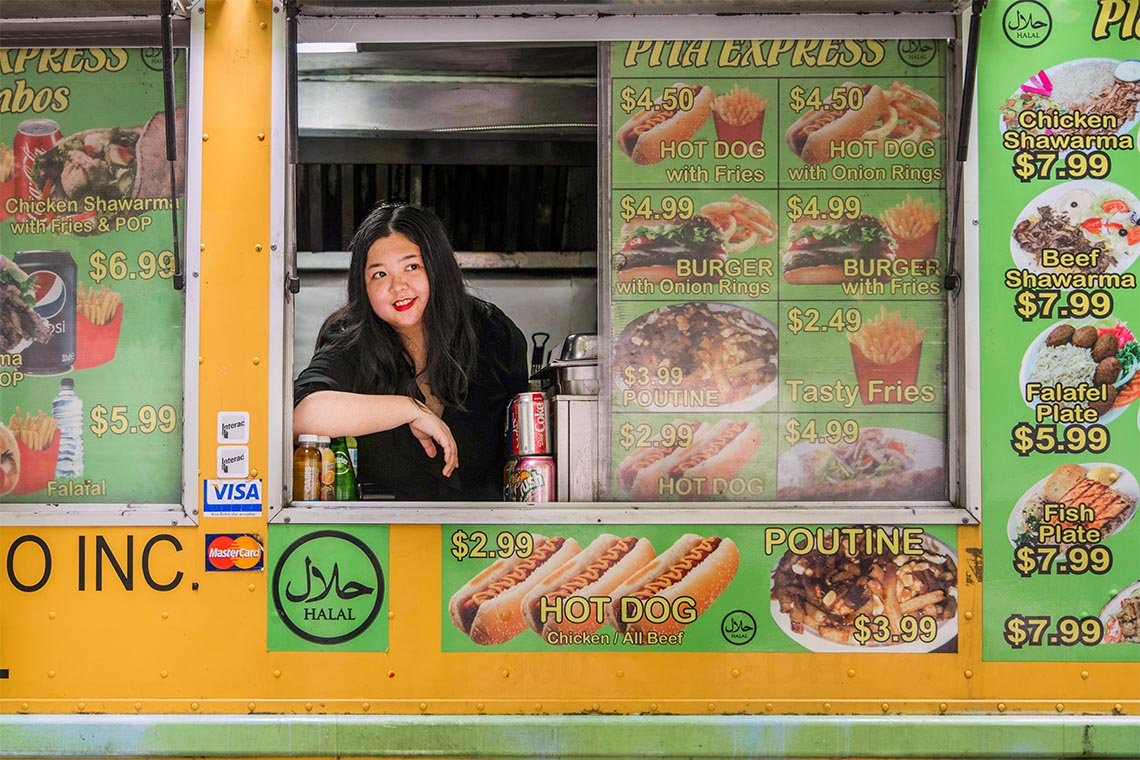 Joanna Luo posing for a portrait in a food truck window