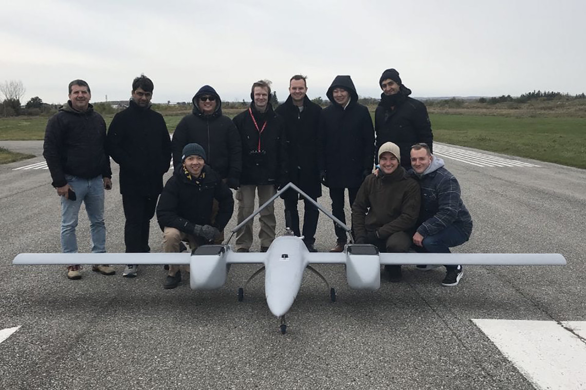 photo of the DX-3 Vanguard drone and the team behind it