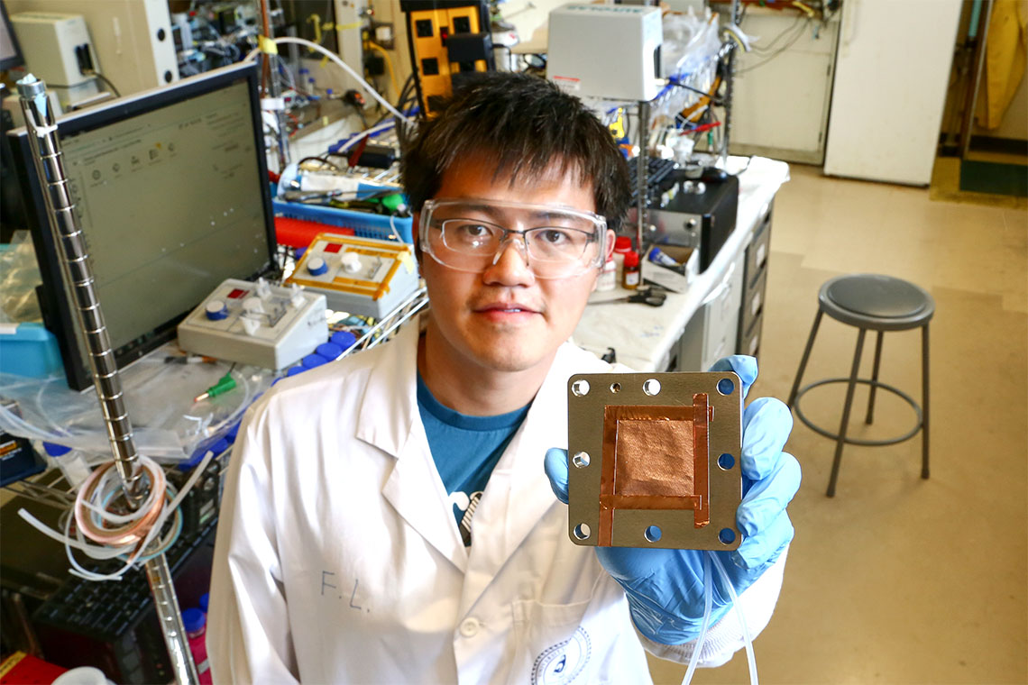 Fengwang Li is holding up an electrolyzer with a copper-based catalyst