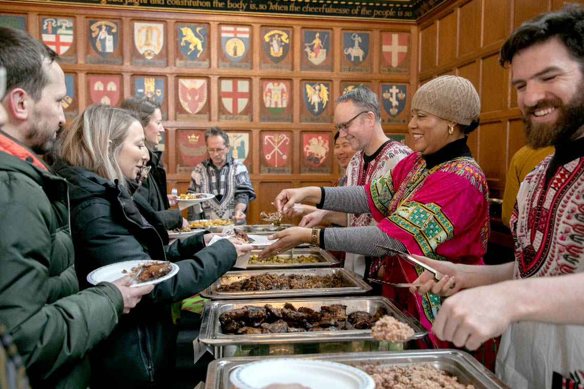 Volunteers serve lunch to eager people in line in the Great Hall at Hart House