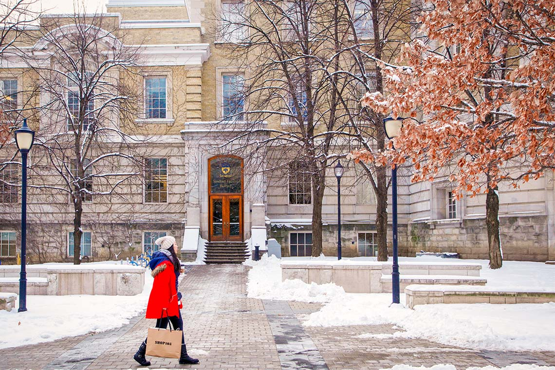 a female student in a red coat walks past a snow-dusted Sanford Fleming building at U of T st george campus