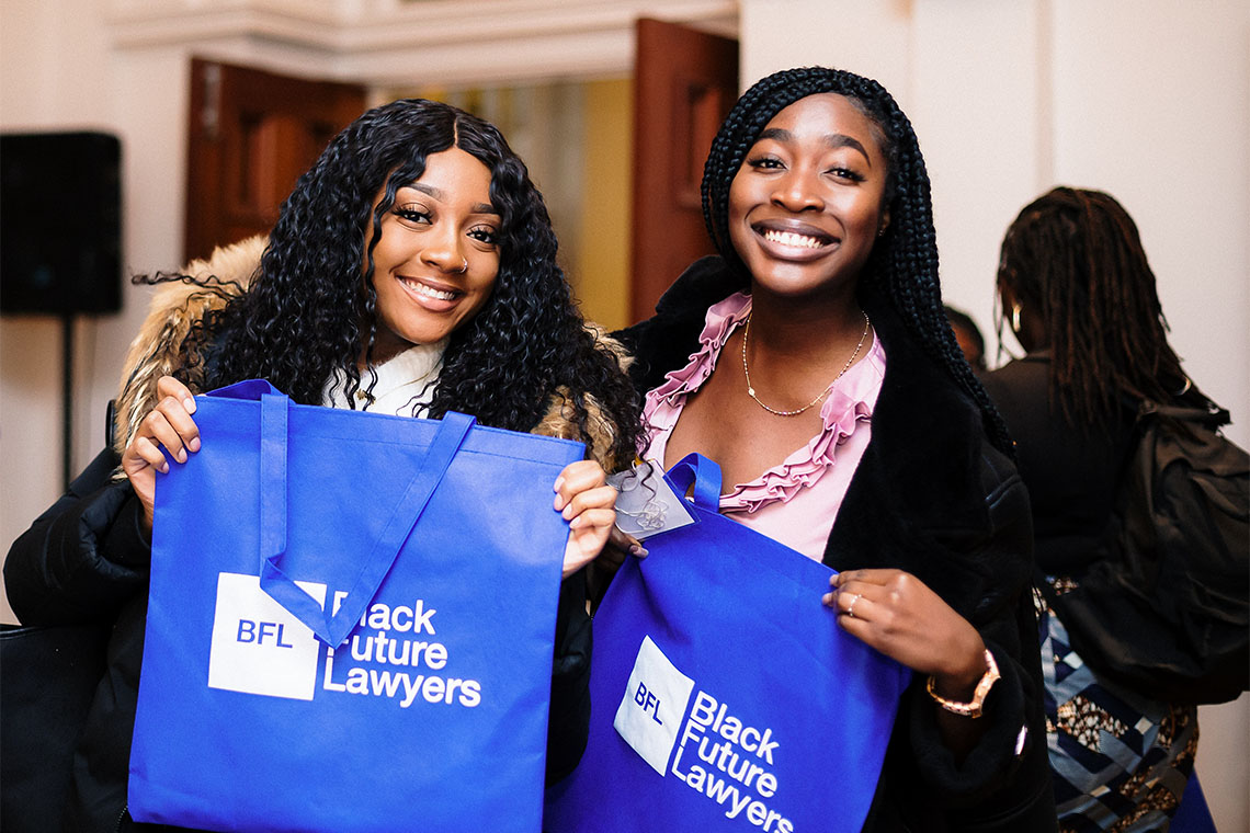 Two smiling women hold up bright blue tote bags that say Black Future Lawyers