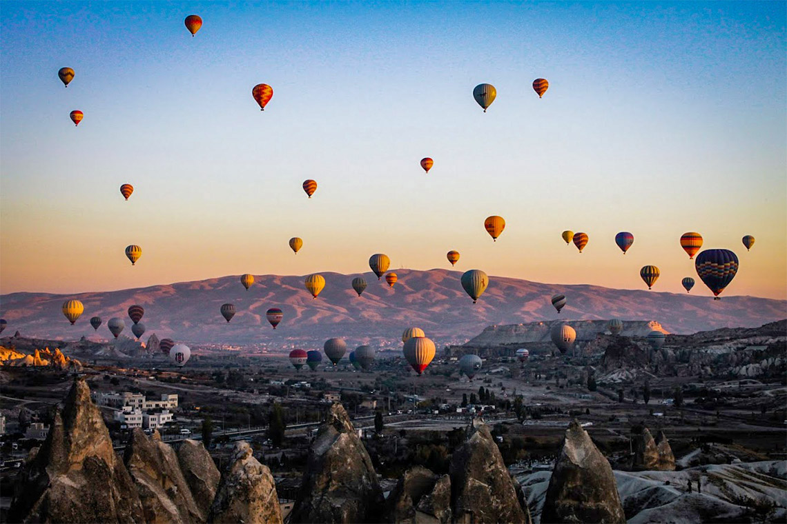 Photo of balloons taking to the sky over  Göreme,Turkey