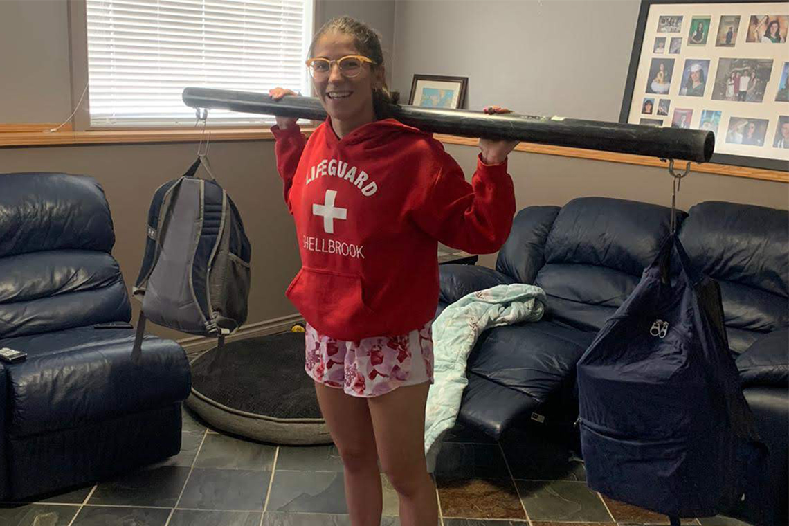 Brenna Hamel weightlifting at home using a pipe and backpacks