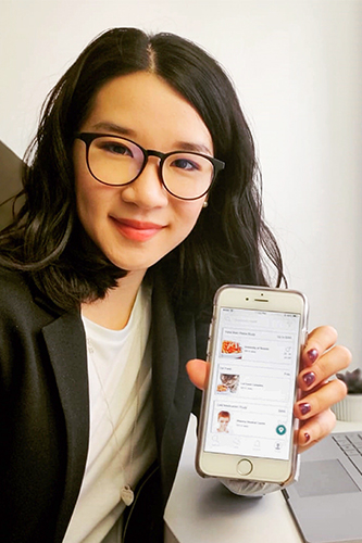 Catherine Chan holds up a cell phone running her honeybee hub app