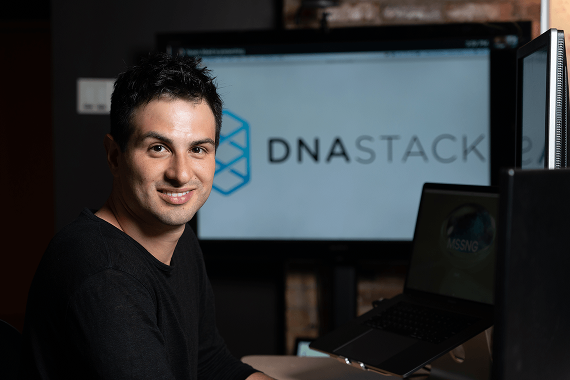 Marc Fiume sits in front of computer monitors displaying the logo of his genomics software startup, DNAstack.