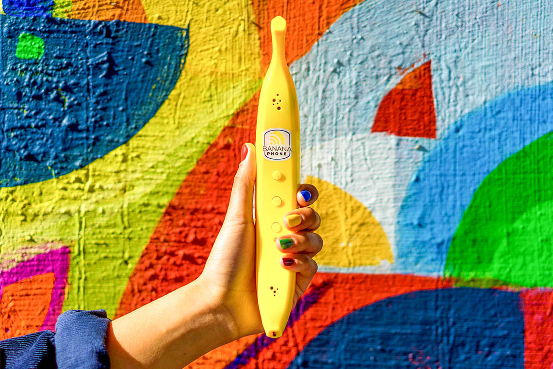 hand holding up a banana phone against a colorful outdoor wall mural