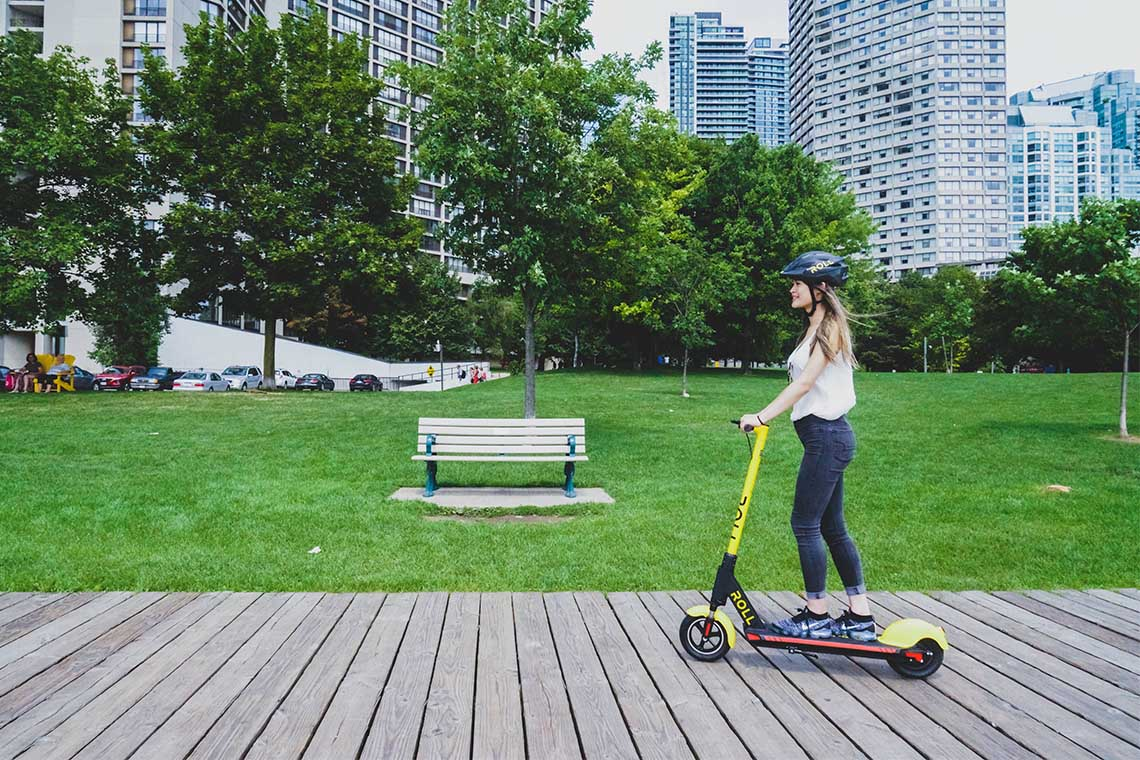 A woman rides a Roll brand e-scooter in Toronto along the boardwalk downtown