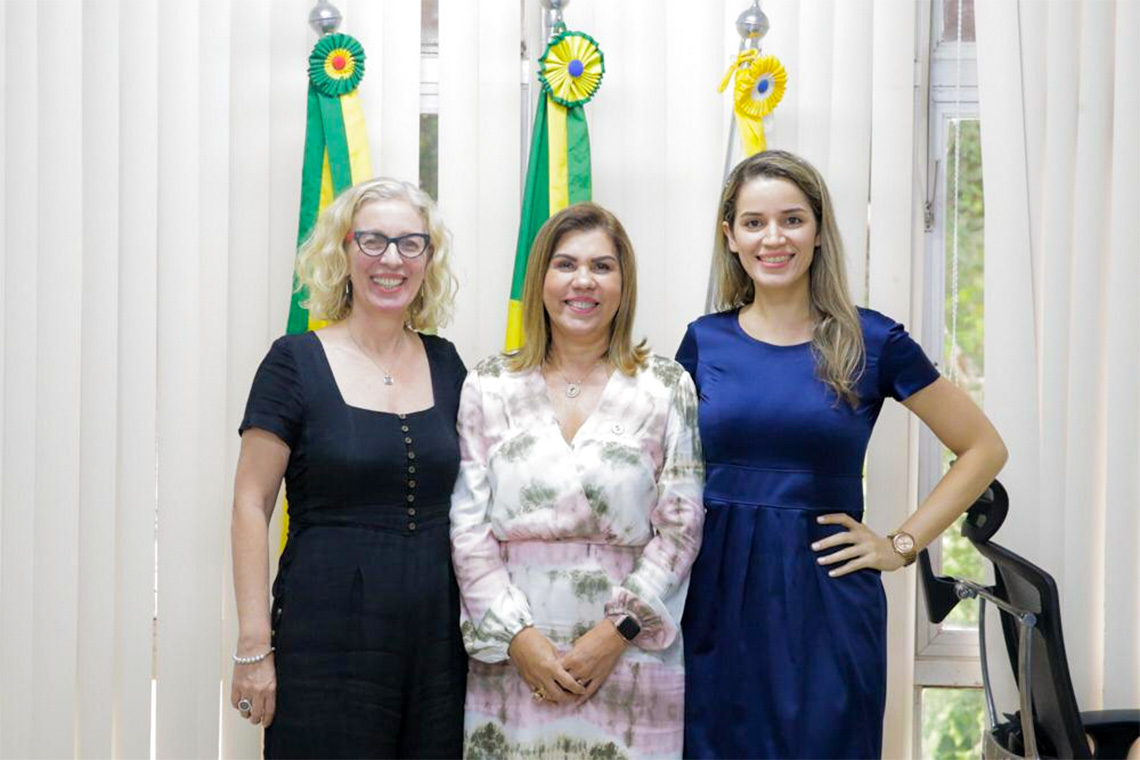 Denise Gastaldo, Margarida de Aquino Cunha and Rozilaine Redi Lago stand in front of flags