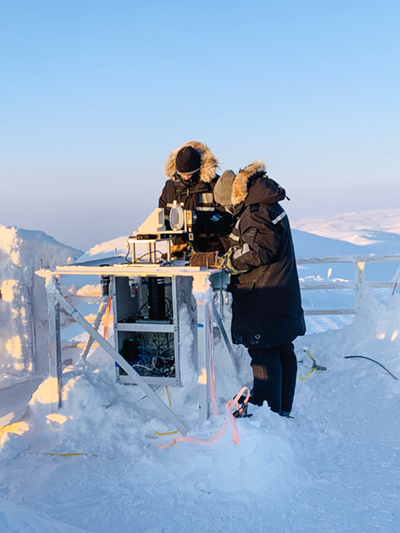 Two grad students troubleshoot an instrument on the roof of the Ridge Laboratory