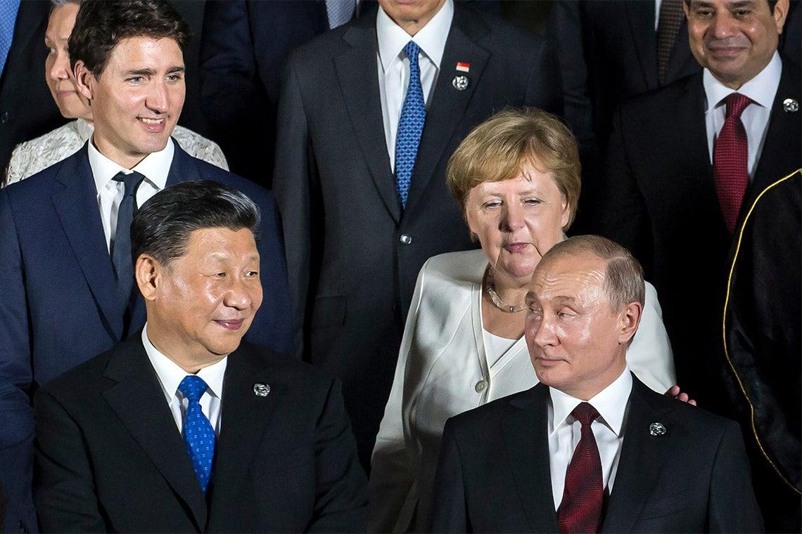 Vladirmir Putin looks back as Justin Trudeau, Angela Merkel and Xi Jinping look towards him