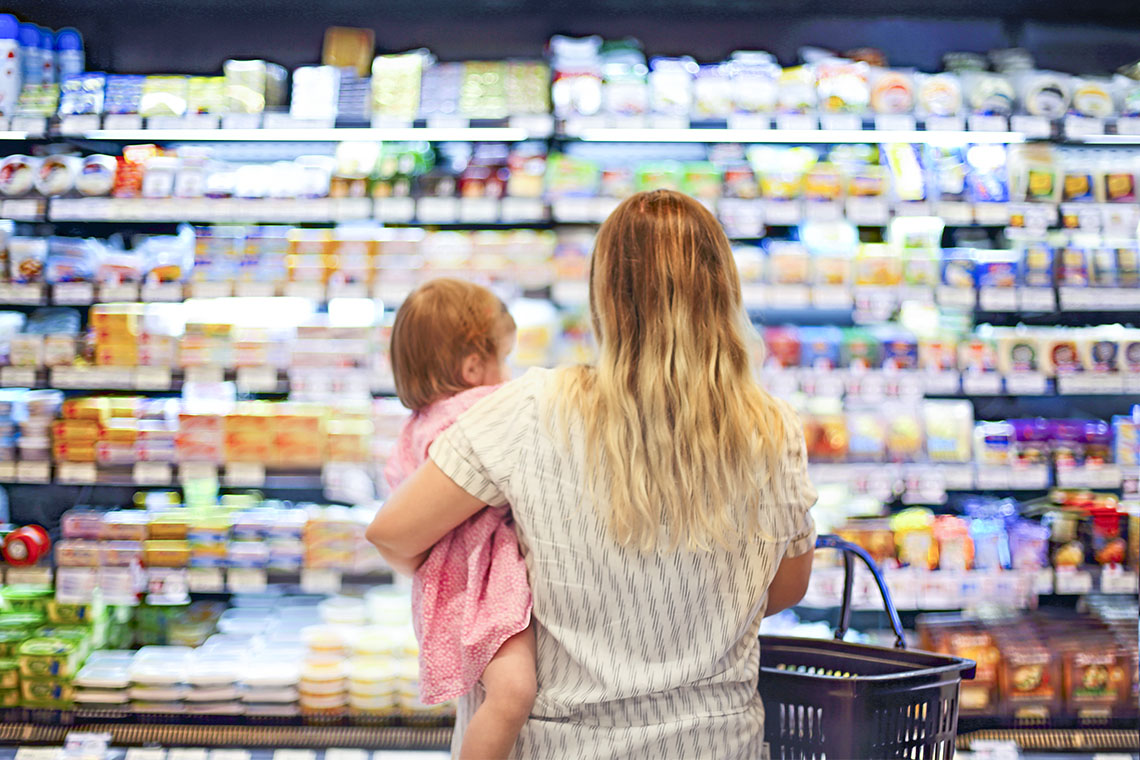 Woman holding a small child at a grocery store