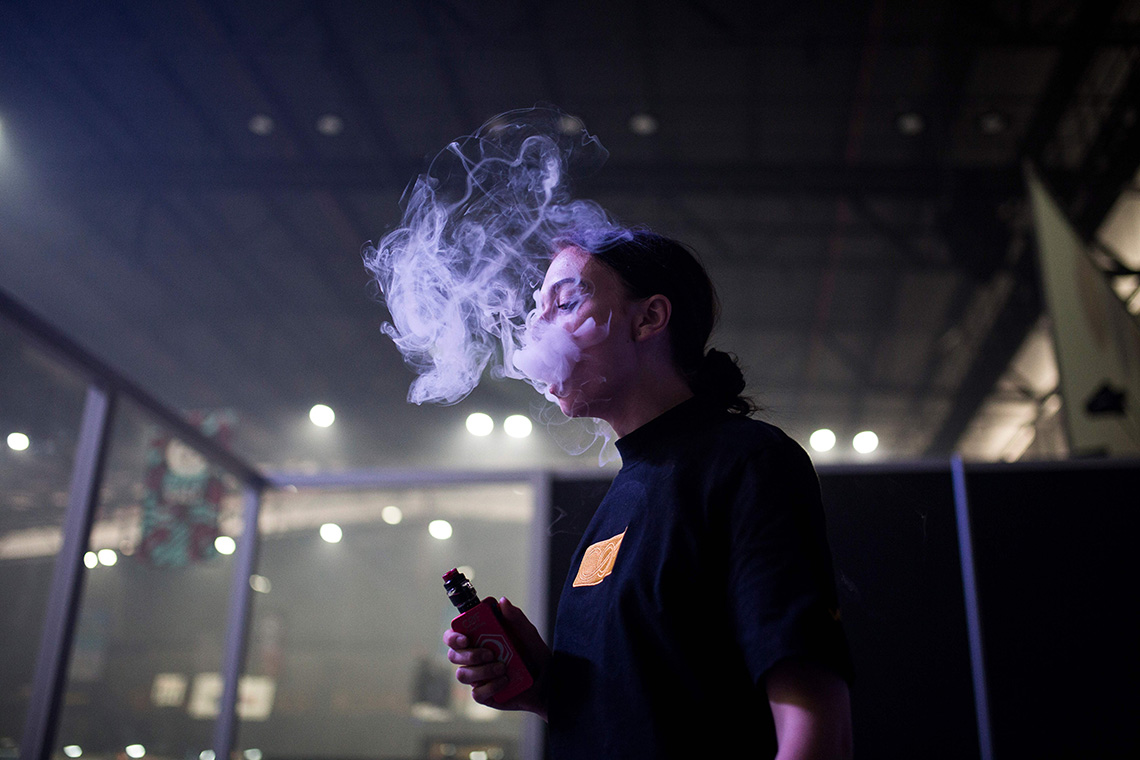 a young person is seen vaping in a dark room
