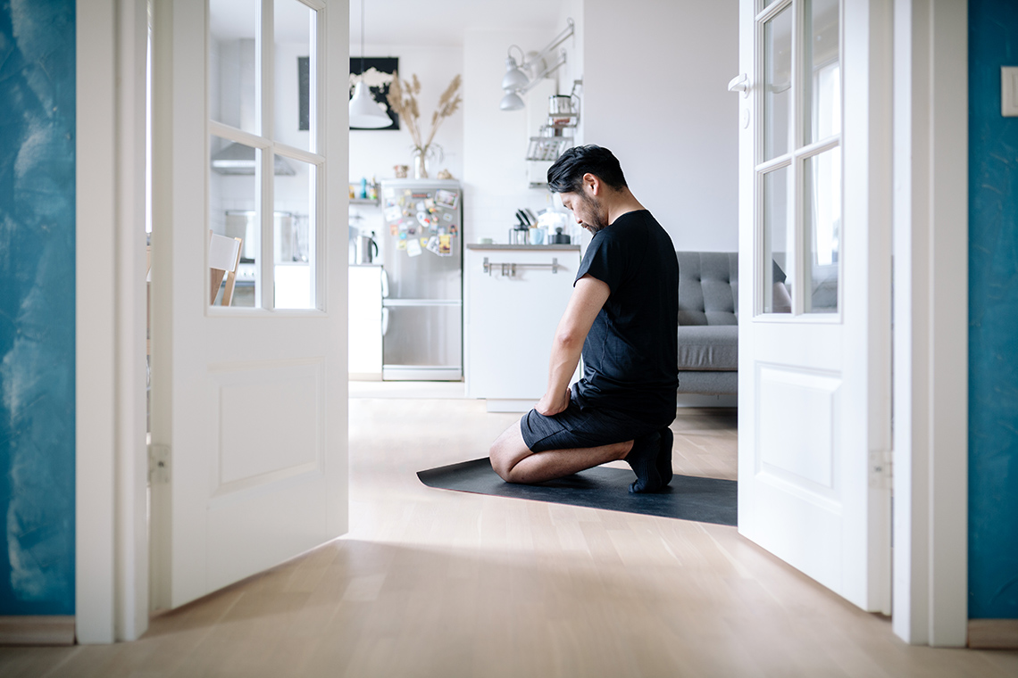 Man meditates while kneeling in his living room