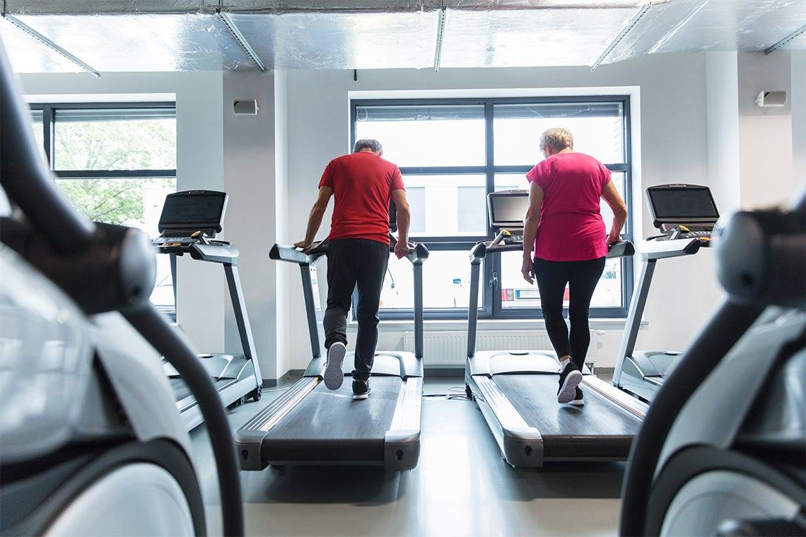 two senior citizens excercising on treadmills