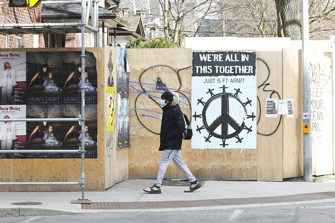 "A solitary man walks past a sign in Parkdale, Toronto that reads ""we're all in this together"""
