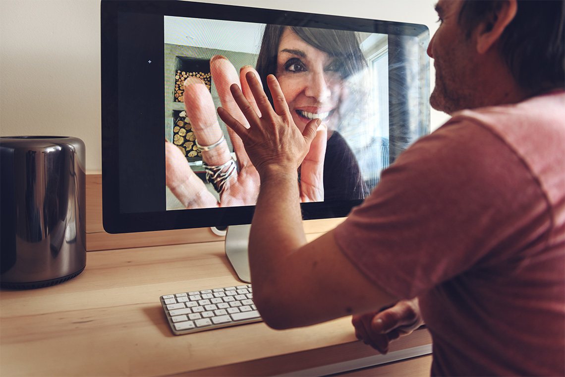 man speaks to woman and virtually press their hands together over video chat