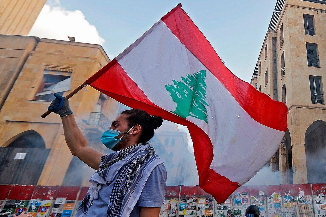 protestor waving a lebanese flag in beirut