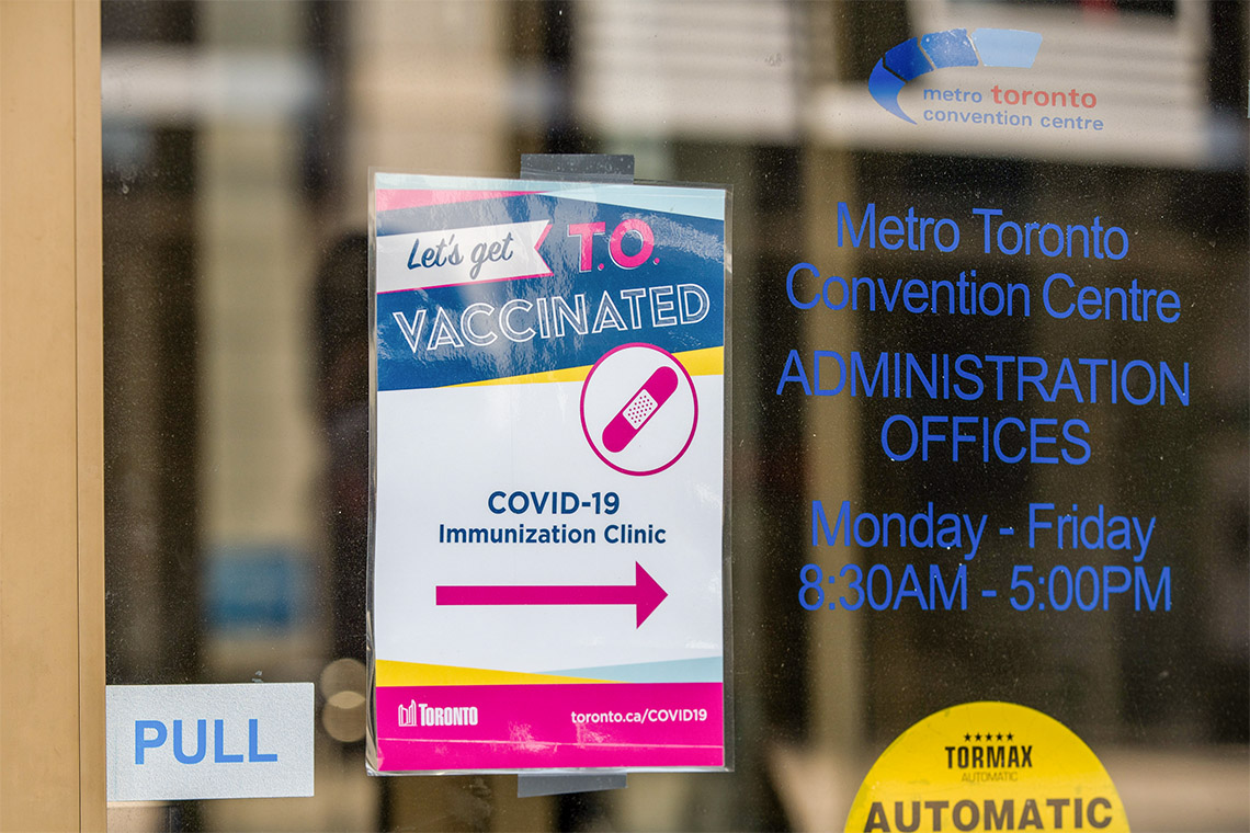 a sign directing people to the metro toronto convention centre vaccine clinic entrance