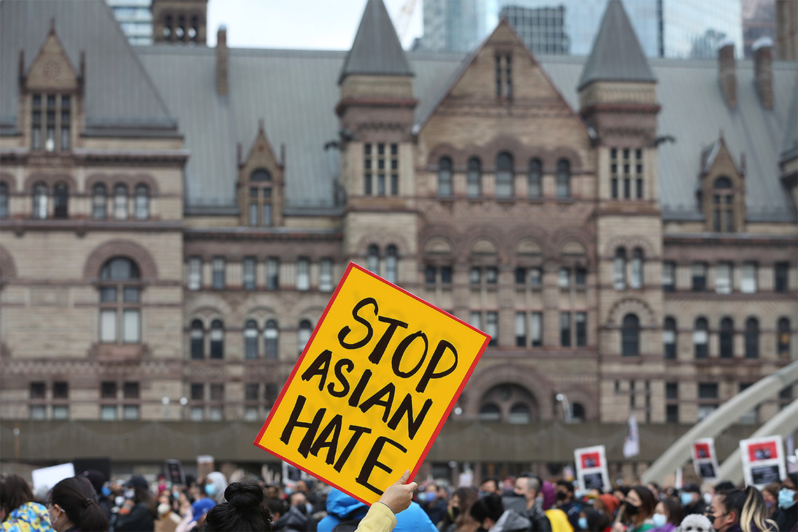 a person holds up a yellow poster that reads Stop Asian Hate. Queen's Park buildings are visible in the background