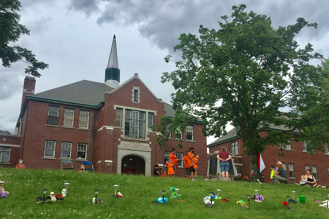 Children's shoes are placed on the ground in front of the Kamloops Residential School