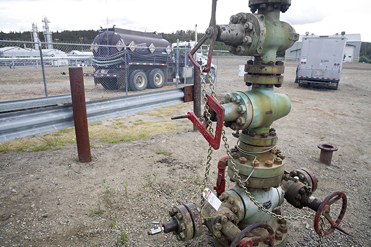 Chained up natural gas wellhead with valves, Northern British Columbia, Canada.
