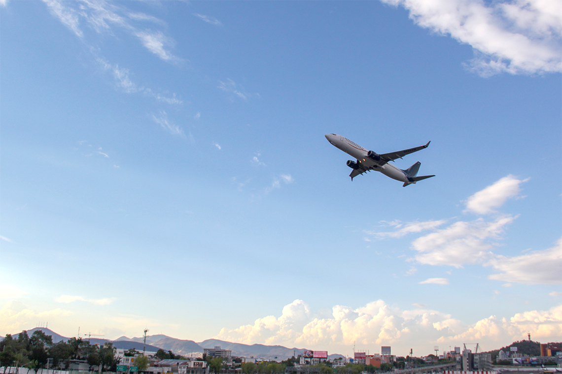 an airplane taking off with mountains and blue sky visible