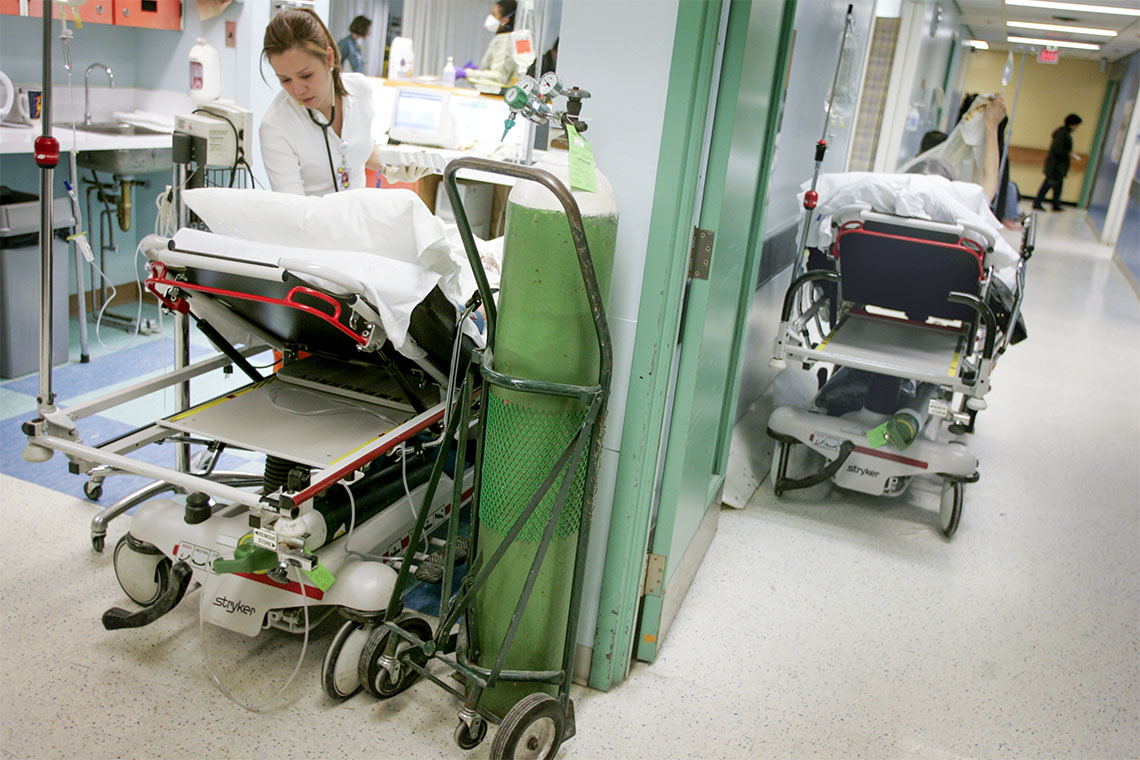 a doctor attends to an anonymous patient while another patient waits on a hospital bed in the hallway of a hospital