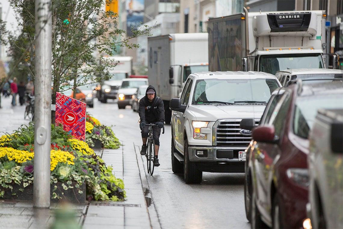 A man rides a bike along a busy Toronto street